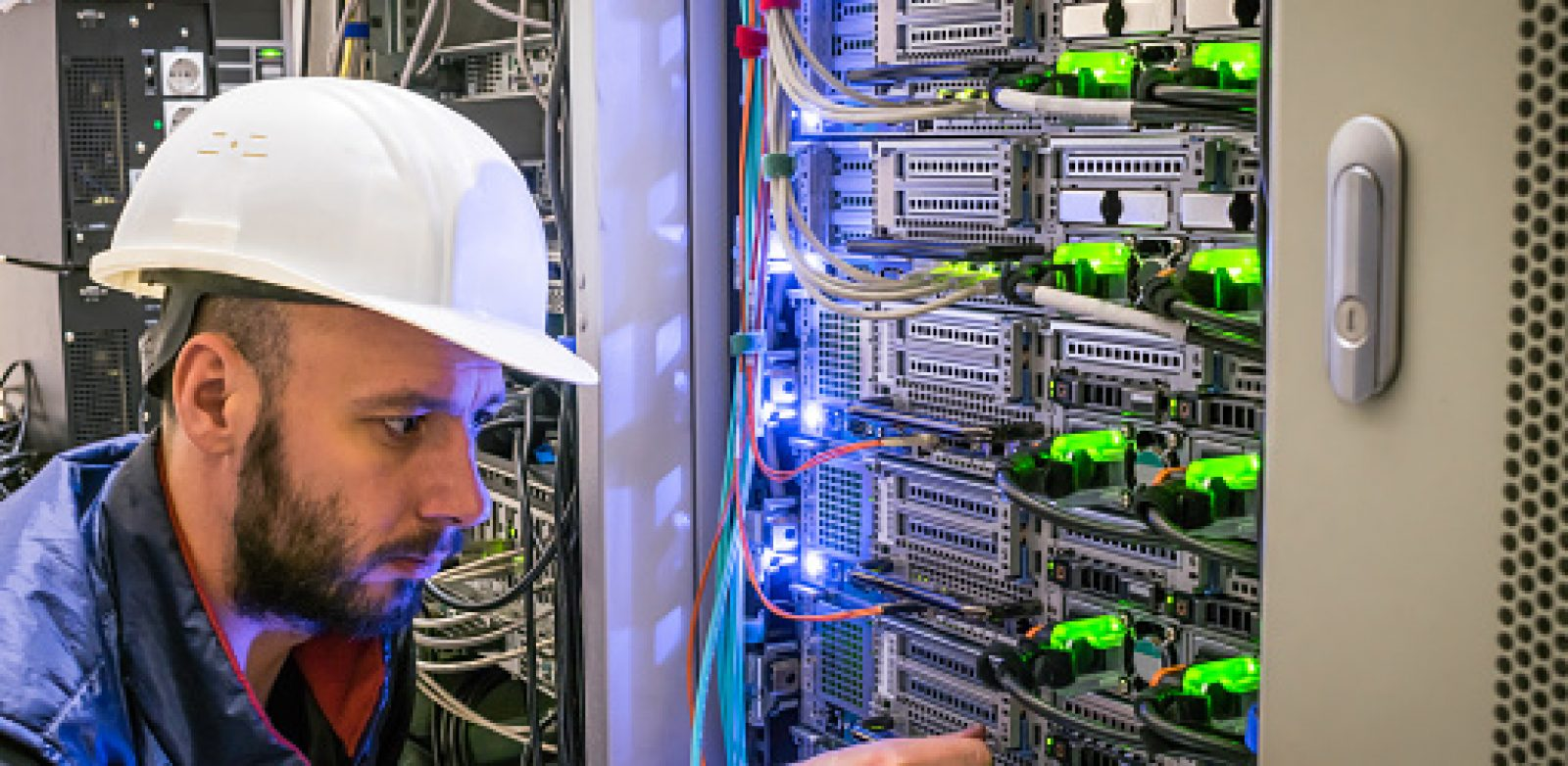A specialist connects the wires in the server room of the data center. A man works with telecommunications. The technician switches the Internet cable of the powerful routers